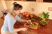 adult woman preparing salad at domestic kitchen poster