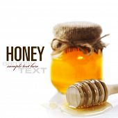Full honey pot and honey stick over white (with sample text)