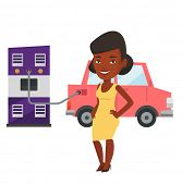 African woman charging electric car at charging station. Woman standing near power supply for electr poster