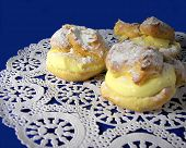 picture of cream puff  - Three lemon custard cream puffs on lace doily - JPG