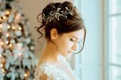 Bride. Wedding. The bride in a short dress with lace in the crown earrings. Wedding bouquet, makeup, poster