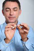 stock photo of quit  - Closeup of man trying to quit smoking - JPG