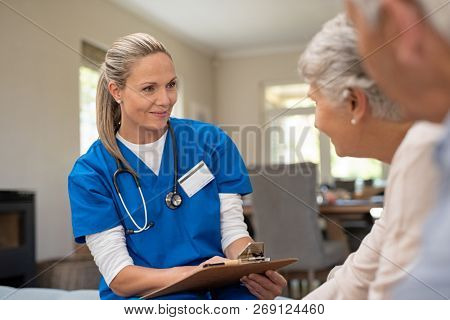poster of Happy nurse talking to senior patients in private clinic. Senior couple consulting health and medica