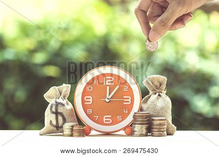 poster of Money Savings, Investment, Time And Money Growing Concept : Hand Holding Coin Over Moneybags And Ora
