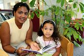 stock photo of storytime  - Child and teacher in a school library - JPG