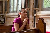 Young woman prying in the church