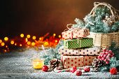Merry Christmas And Happy New Year. Basket With Christmas Toys And Christmas Gifts On A Wooden Backg poster