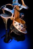 High-heeled Shoes For Dancing And Striptease Stand On A Glass Reflective Surface. Champagne-colored  poster