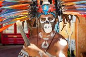TULUM, MEXICO - JULY 15: Unknown man in Mayan traditional ornamental feather headdress playing on dr