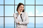 Gorgeous Woman Talking On Phone. Young Pretty Business Lady With Cell Phone On Office Window Backgro poster