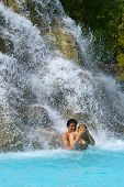 Mixed couple bathing near waterfall