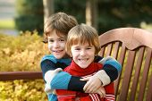 foto of cute kids  - Brothers Hugging Sitting on a Park Bench - JPG