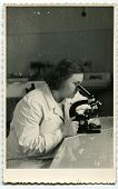 Vintage photo of young female doctor with microscope (early fifties)