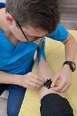 Physiotherapist Applying Kinesiology Tapes On Injury Leg poster