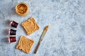 Two tasty peanut butter toasts placed on stone table. With small jars of fruit jam big peanut butter poster