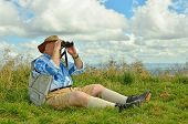 Senior birdwatcher looking by binoculars