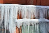 Long, Big And Dangerous Icicles On A Brick House Roof poster