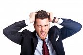 stock photo of angry man  - Angry businessman with hands in his hair isolated on white - JPG