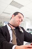 Young man strangling himself with a telephone cord in an office environment