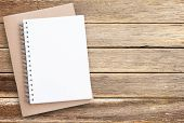 Blank Paper Notebook On Brown Wooden Table Background. Top View With Copy Space (selective Focus). O poster