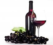 Red wine: bottle, glass and black grapes