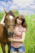 La imagen de una hermosa chica morena con caballo