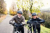 Active Senior Couple With Electrobikes Standing Outdoors On A Road In Nature. poster