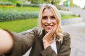 Image of joyous woman 20s wearing jacket smiling and taking selfie photo while walking through park poster