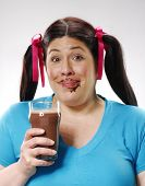 One fat girl holding a chocolate glass. dirty chocolate mouth.