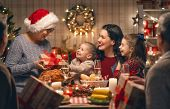 Merry Christmas! Happy family are having dinner at home. Celebration holiday and togetherness near t poster