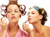 Two young women applying makeup mirror.
