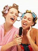 Duas mulheres jovens engraçadas cantando com um pentes