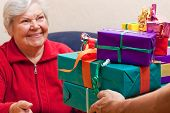 Female Senior Sits And Gets Or Give Many Gifts
