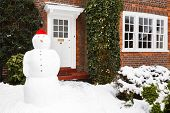 stock photo of entryway  - Snowman in front garden of home in winter - JPG