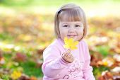 Portrait Of A Beautiful Little Girl Holding A Maple Leaf In His Hand
