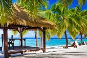 foto of deserted island  - Tropical gazebo with chairs on deserted beach with palm trees - JPG
