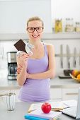Happy Teenage Girl Eating Chocolate While Studying In Kitchen