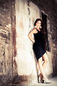 stock photo of little black dress  - a beautiful brunette woman leaning against an old wall with her hands behind her back wearing a little black dress and big golden earings - JPG