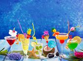 Colorful varied tropical Cocktails in tropical blue wood with coconut mojito peppermint margarita