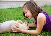 children girl playing with chihuahua dog lying on backyard lawn