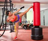 image of heavy bag  - Crossfit fitness woman kick boxing with red punching bag at gym - JPG