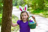 Easter girl with eggs basket and funny bunny ears on the forest
