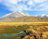 The huge valley surrounded by snow-capped mountains. Crosses the picturesque valley of the creek. Th