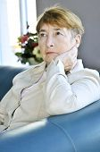 image of old lady  - Sad elderly woman sitting on a couch indoors - JPG