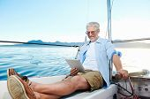 sailing man reading tablet computer on boat with modern technology and carefree retired senior succe
