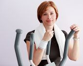 Sporty adult, healthy lifestyle - woman at the gym on a crosstrainer.