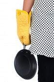 A woman holding a frying pan by her side. She is wearing a polka dot apron and a yellow oven mitt. V