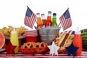 A picnic table set up with a Fourth of July theme. Horizontal format with a white background. Items include a soda bucket, hot dog, watermelon, chips, pretzels, and American Flag accessories.