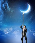 Image of businessman climbing rope attached to moon