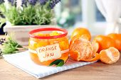 Orange jam with zest and tangerines, on wooden table